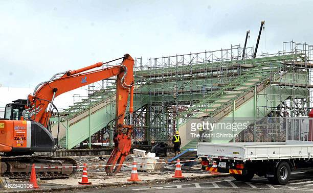 Workers prepare to dismantle a bridge connecting platforms at JR Tomioka Station on January 26 2015 in Tomioka Fukushima Japan According to the...