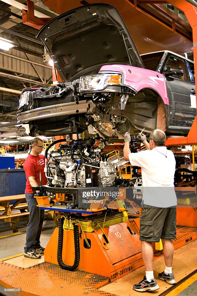 Workers prepare to insert the engine and drivetrain into the frame for a new Ford Flex as it makes its way down the assembly line at the Ford Motor...