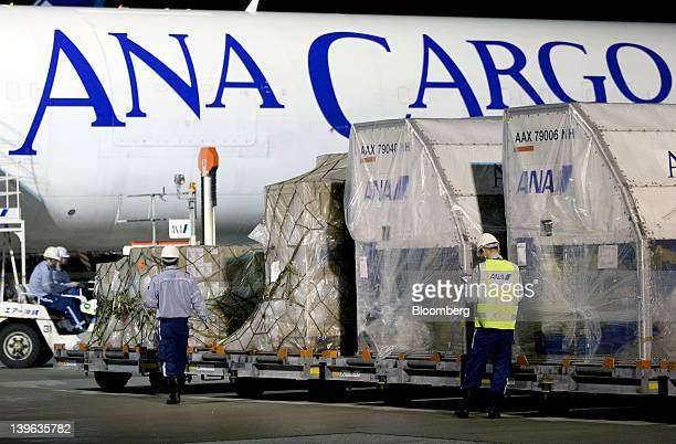 Workers prepare to load air containers onto an All Nippon Airways Co cargo aircraft at the company's cargo hub terminal at Naha Airport in Naha City...