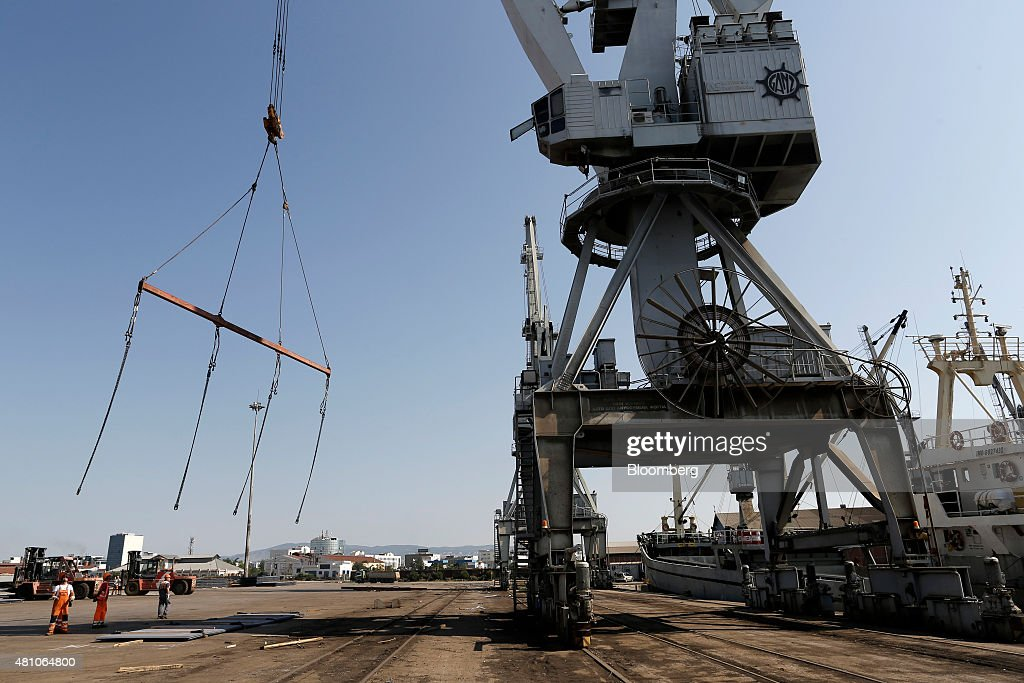 Workers prepare to load sheets of metal onto a cargo ship as a winch is lowered on the dockside at Thessaloniki port operated by Thessaloniki Port...