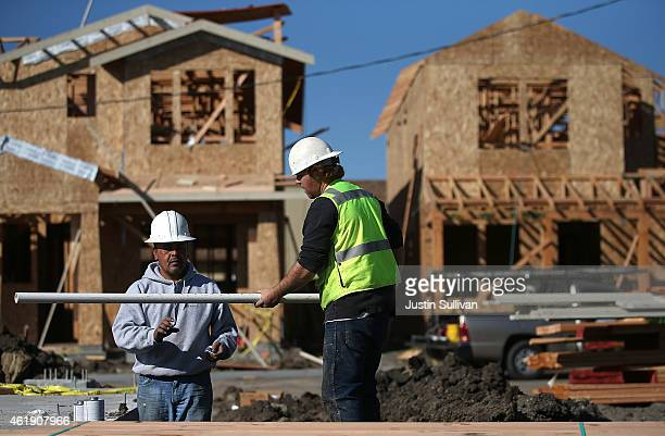 Workers prepare to move a piece of pipe into place as they build a new home on January 21 2015 in Petaluma California According to a Commerce...