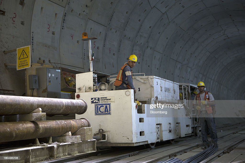 Workers prepare to move steel pipes inside a finished section of the Tunnel Emisor Oriente (TEO), or Eastern Discharge Tunnel, during construction of the 38 mile (62km) underground wastewater treatment tunnel in Mexico City, Mexico, on Thursday, Sept. 12, 2013. The tunnel, which is expected to be completed in 2014, will boost Mexico City's drainage capacity to help prevent flooding during rainy season and the over-exploitation of groundwater resources. The project is being managed by Mexico's National Water Commission, Conagua. Photographer: Susana Gonzalez/Bloomberg via Getty Images