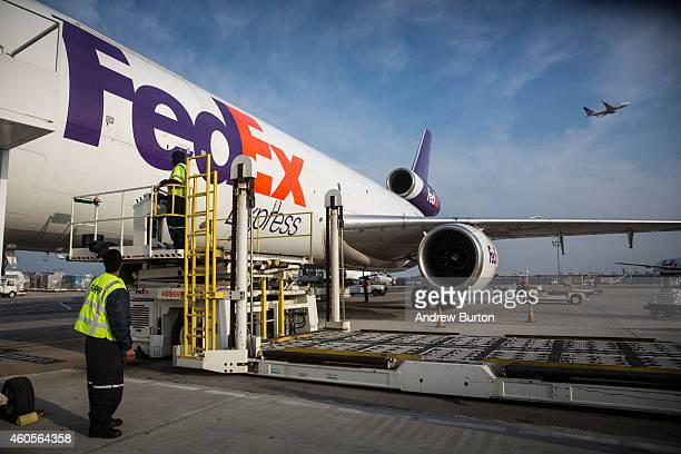 Workers prepare to offload an incoming FedEx plane at a FedEx global hub one of only seven in the US on December 16 2014 in Newark New Jersey FedEx...