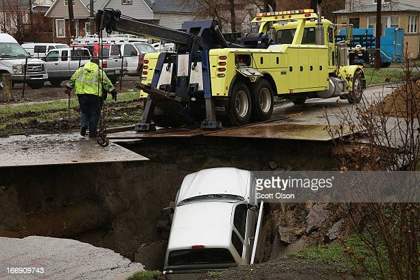 Workers prepare to pull a truck from a sinkhole that opened up on a residential street in the South Deering neighborhood on April 18 2013 in Chicago...