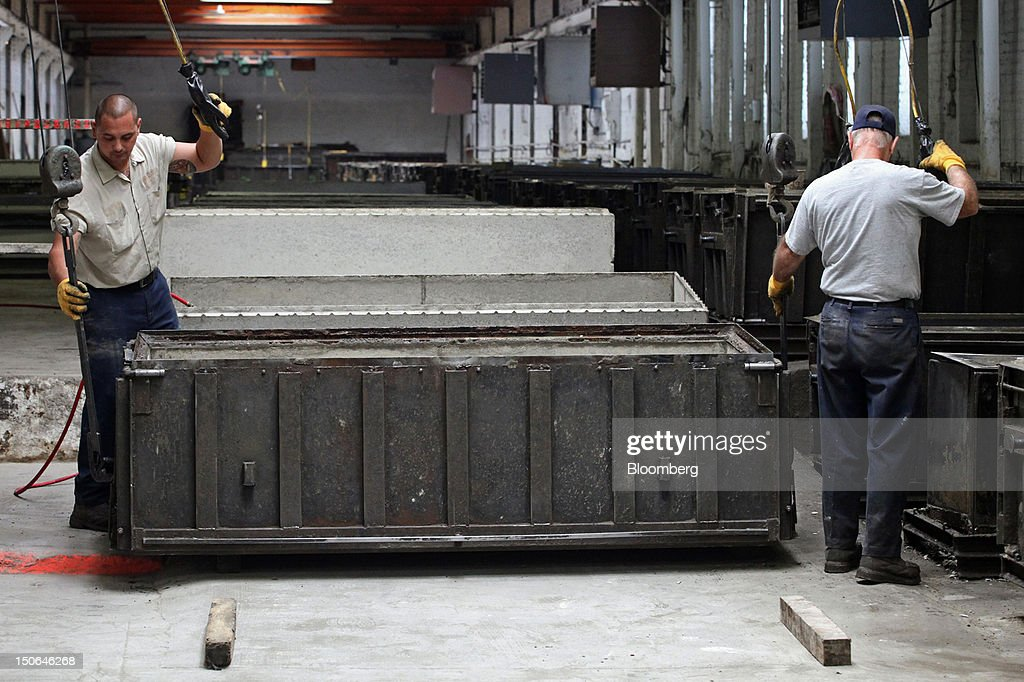 Workers prepare to remove a concrete form from a burial vault at the American Wilbert Vault Corp. manufacturing facility in Des Plaines, Illinois, U.S., on Thursday, Aug. 23, 2012. Several U.S. Presidents including John F. Kennedy and Ronald Reagan, and other famous people including Al Capone, Louis Armstrong, Elvis Presley and Frank Sinatra are buried in American Wilbert burial vaults, according to the company. The U.S. Census Bureau is expected to release data on orders for durable goods on Aug. 24. Photographer: Tim Boyle/Bloomberg via Getty Images