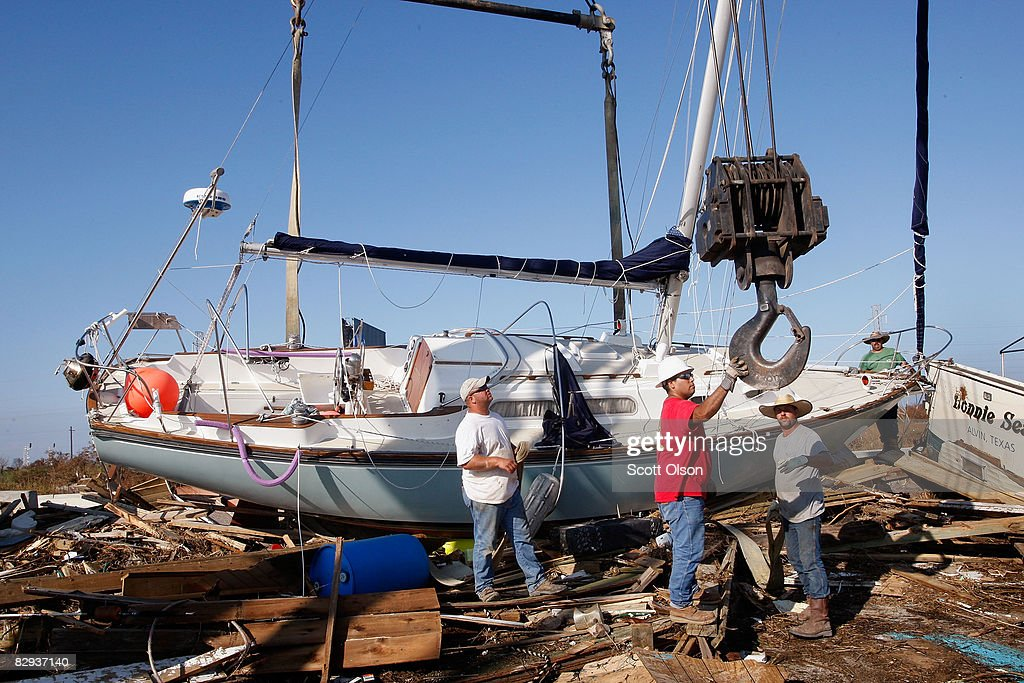 Workers prepare to remove a sailboat washed up onto the edge of the highway into Galveston by Hurricane Ike September 21 2008 in Galveston Texas The...