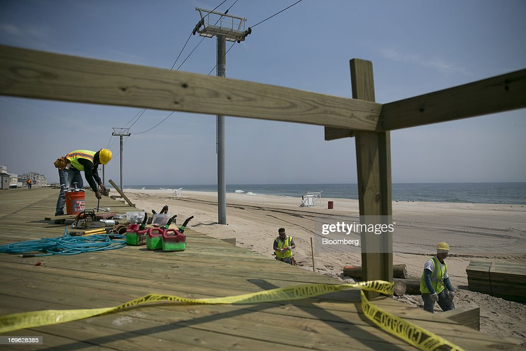 Workers prepare to repair a section of the boardwalk in Seaside Heights, New Jersey, U.S., on Wednesday, May 29, 2013. Sandy, which came ashore near Atlantic City, killed dozens of people and destroyed more than 365,000 homes in the state. Christie has said it will cost $36.9 billion for repairs and to prevent devastation from future storms. Photographer: Scott Eells/Bloomberg via Getty Images