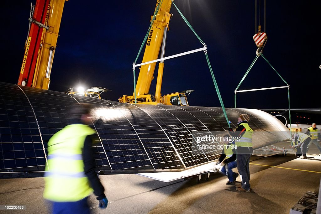 Workers prepares to load a wing of the Swiss sun-powered aircraft Solar Impulse into a Cargolux Boeing 747 cargo aircraft on February 20, 2013 at Payerne airport. The Boeing will carry Solar Impulse HB-SIA prototype aircraft to San Francisco for a serie of flights across America from the West to East Coast. AFP PHOTO / FABRICE COFFRINI