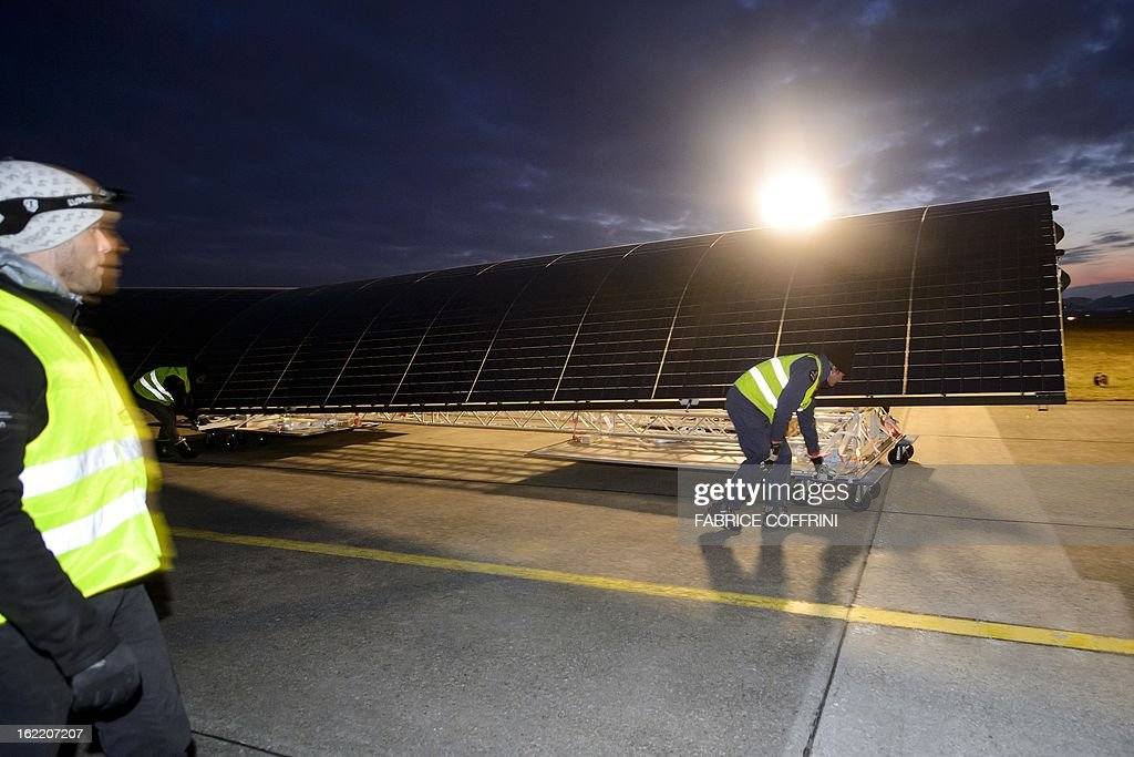 Workers prepares to load a wing of the Swiss sun-powered aircraft Solar Impulse into a Cargolux Boeing 747 cargo aircraft on February 20, 2013 at Payerne airport. The Boeing will carry Solar Impulse HB-SIA prototype aircraft to San Francisco for a serie of flights across America from the West to East Coast.