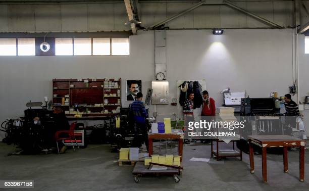 Workers print books and flyers at a printing company in Kurdishmajority Qamishli in northeast Syria on January 11 2017 For years Syria's Kurds were...