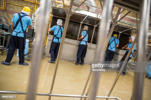 Workers process dehydrated garlic at the Nithi Foods Co factory in the San Pa Tong district of Chiang Mai Thailand on Tuesday May 23 2017 Thailand's...