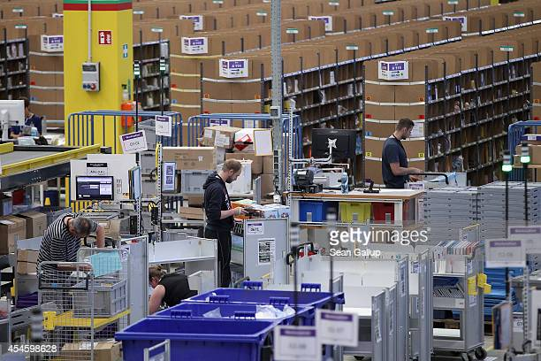 Workers process incoming inventory at an Amazon warehouse on September 4 2014 in Brieselang Germany Germany is online retailer Amazon's second...