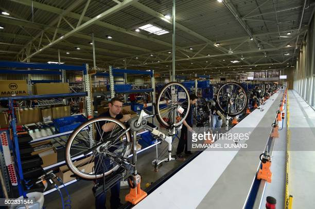 Workers produce electric bicycles at the factory of Dutch bicycle manufacturer Gazelle in Dieren The Netherlands on December 10 2015 On the busy...