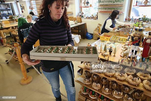 Workers produce handcrafted wooden figurines at the Richard Glaesser GmbH Erzgebirgische Volkskunst ateliers on November 25 2014 in Seiffen Germany...