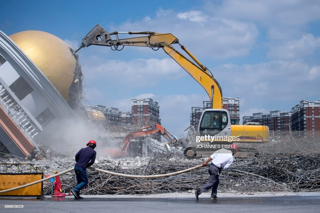Workers Pull A Water Hose At The Demolition Site Of The Jiuxing Furniture  Market In The