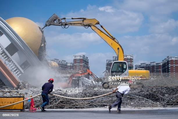 Workers pull a water hose at the demolition site of the Jiuxing furniture market in the suburbs of Shanghai on May 22 2017 The market used to consist...