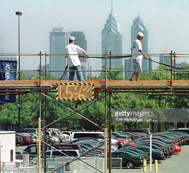 Workers pull audio and video cables across an overpass built in the parking lot of the First Union Center 22 July 2000 in Philadelphia site of the...
