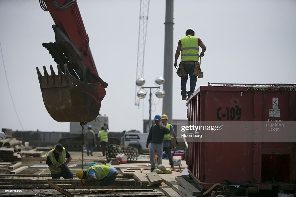 Workers pull old lumber out of a section of the boardwalk during reconstruction in Seaside Heights, New Jersey, U.S., on Wednesday, May 29, 2013. Sandy, which came ashore near Atlantic City, killed dozens of people and destroyed more than 365,000 homes in the state. Christie has said it will cost $36.9 billion for repairs and to prevent devastation from future storms. Photographer: Scott Eells/Bloomberg via Getty Images