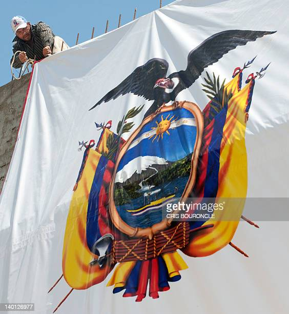 Workers pull up a gigantic banner with the Ecuadorean national emblem on February 28 in a main street of the city of Chiclayo 760 km north of Lima...