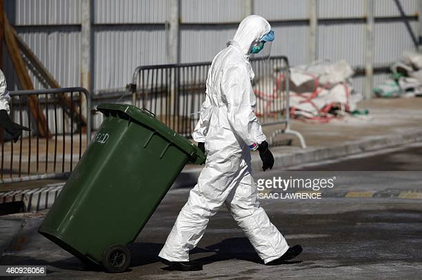 A workers pulls a bin during a chicken cull in Hong Kong on December 31 after the deadly H7N9 virus was discovered in poultry imported from China...