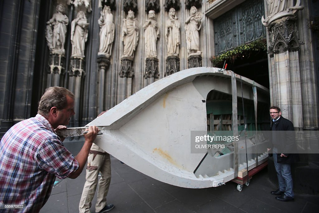 Workers push a seven-meters long refugee boat through the entrance portal of the Cologne Cathedral on May 31, 2016 in Cologne, western Germany. The boat, that served as altar during the 2016 Corpus Christi service held outside the Cathedral, will stay inside the church as a memorial during the 'Year of Mercy' proclaimed by Pope Francis. Several years ago, 80 to 100 people had managed to flee in the boat from Libya to Europe. / AFP / dpa / Oliver Berg / Germany OUT
