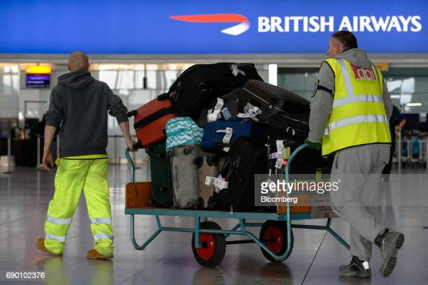 Workers push a trolley of suitcases and bags through departures at the British Airways terminal Terminal 5 at London Heathrow Airport in London UK on...