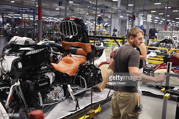 Workers put finishing touches on an Indian Roadmaster motorcycle at the end of the assembly line at the Polaris Industries factory on August 8 2014...