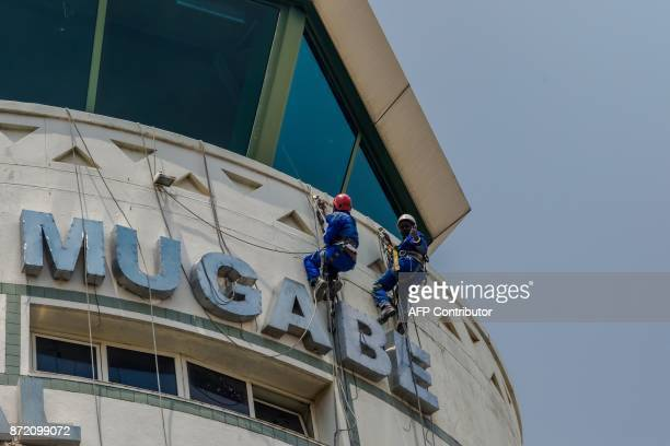 Workers put finishing touches on the new sign at Zimbabwe's main international airport in Harare renamed after Zimbabwean President Robert Gabriel...