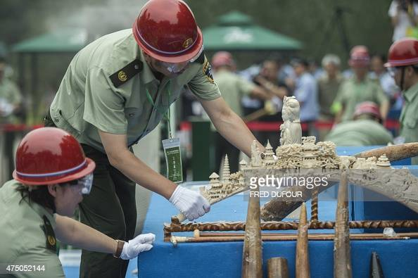 Workers put ivory items on a sliding belt before being destroyed in Beijing on May 29 2015 China destroyed more than six hundred kilograms of ivory...