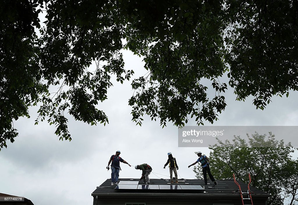 Workers put solar panels down during an installation May 3, 2106 in Washington, DC. The installation marked the one millionth in the U.S. in the past 40 years. It has been predicted that the U.S. will reach 2 million installations in two years.