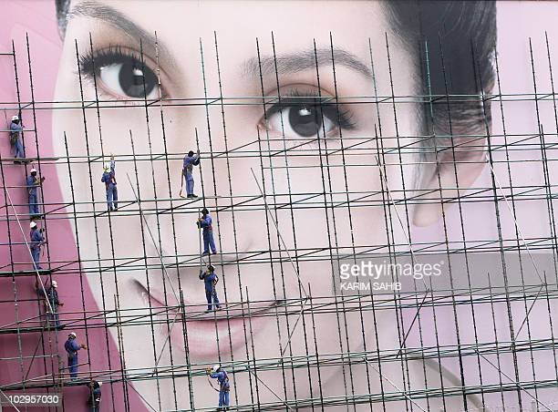 Workers put the finishing touches on a massive billboard advertisement at a shopping center in Dubai on July 14 2010 AFP PHOTO/KARIM SAHIB