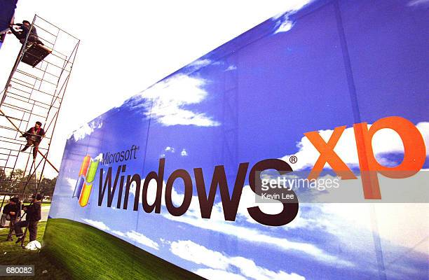 Workers put the finishing touches on a Microsoft billboard featuring its latest software Windows XP at the entrance of a conference center November 7...