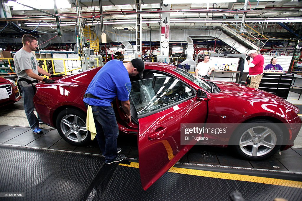 Workers put the finishing touches on a new General Motors 2016 Chevrolet Camaro as it rolls off the production line at GM's Lansing Grand River...
