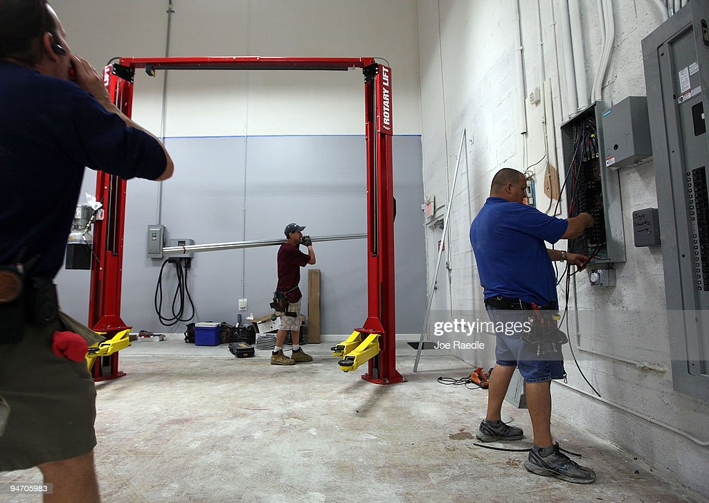 Workers put the finishing touches on the garage area of the Tesla Motors first South Florida location on December 17, 2009 in Dania Beach, Florida. Tesla produces high-performance electric vehicles with a fully electric power train.