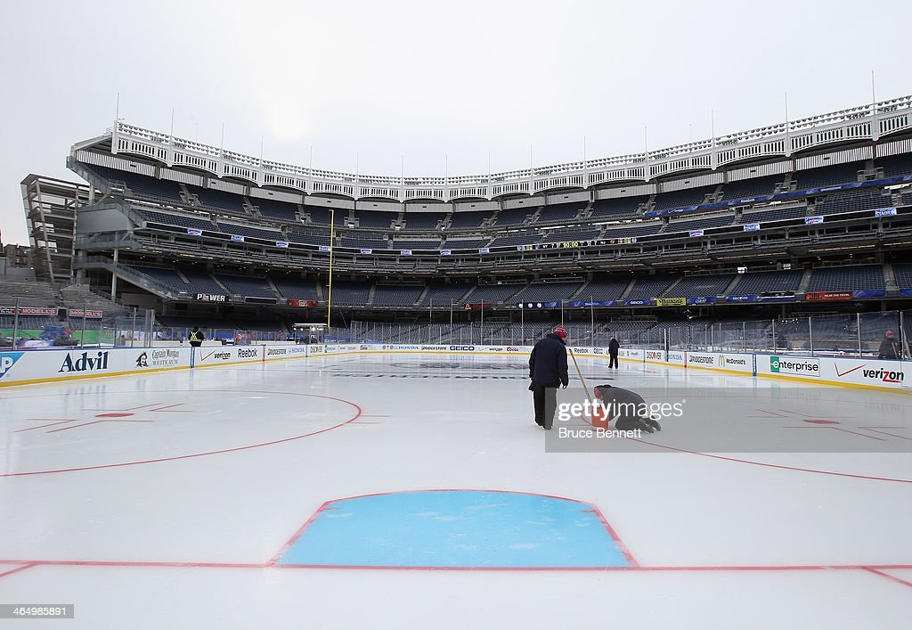 Workers put the finishing touches on the ice rink prior to player and family skates the day before the outdoor game between the New York Rangers and the New Jersey Devils at Yankee Stadium on January 25, 2014 in the Bronx borough of New York City.