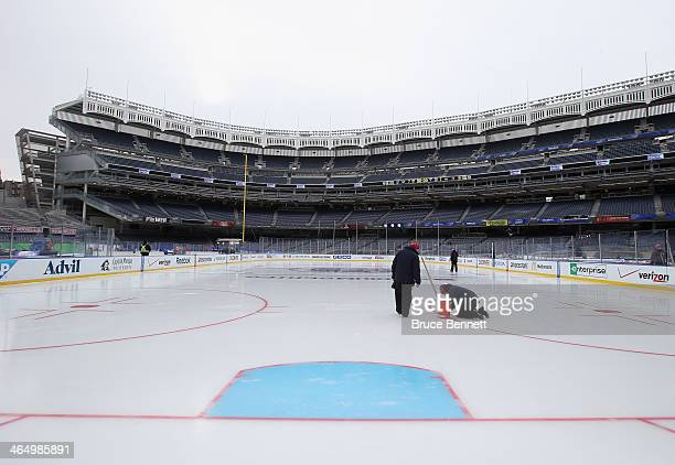 Workers put the finishing touches on the ice rink prior to player and family skates the day before the outdoor game between the New York Rangers and...