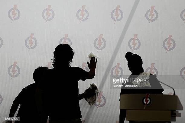 Workers put up finishing touches to the the People's Action Party backdrop before the start of the party lunch time rally in the heart of Central...
