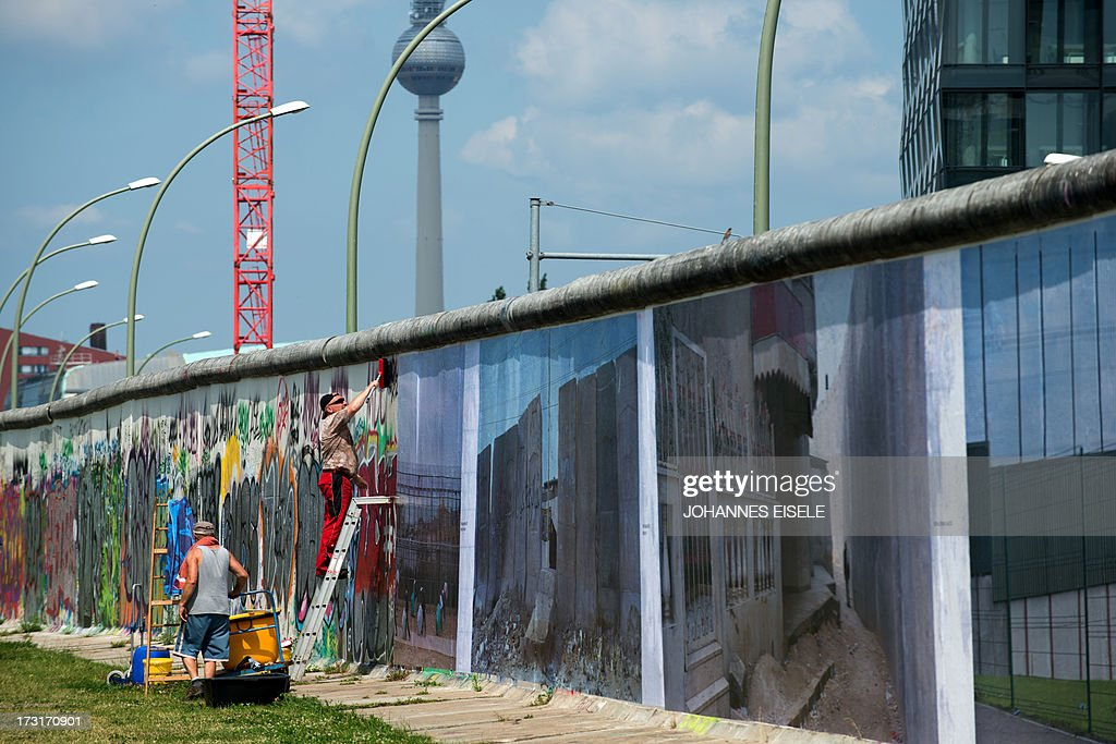 STORY - Workers put up panorama pictures of German photographer Kai Wiedenhoefer that are part of his 'Wall on Wall' exhibition on a remaining section of the Berlin Wall in Berlin, Germany on July 9, 2013. The 'Wall on Wall' project by award-winning German photographer Kai Wiedenhoefer features giant panoramas taken in Northern Ireland, Iraq, Cyprus, the West Bank, Morocco, South Korea and the border zone between the United States and Mexico.