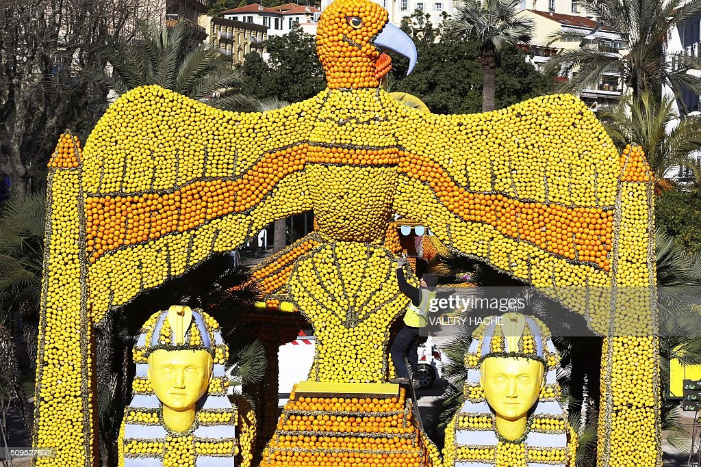 A workers puts the final touch on a sculpture decorated with oranges and lemons are pictured in Menton on the French Riviera on February 11, 2016, ahead of the start of the 'Fete du Citron' (Lemon Festival). The theme of this 83rd edition, running from February 13 until March 2, 2016, is called 'Cinecitta'. / AFP / VALERY HACHE