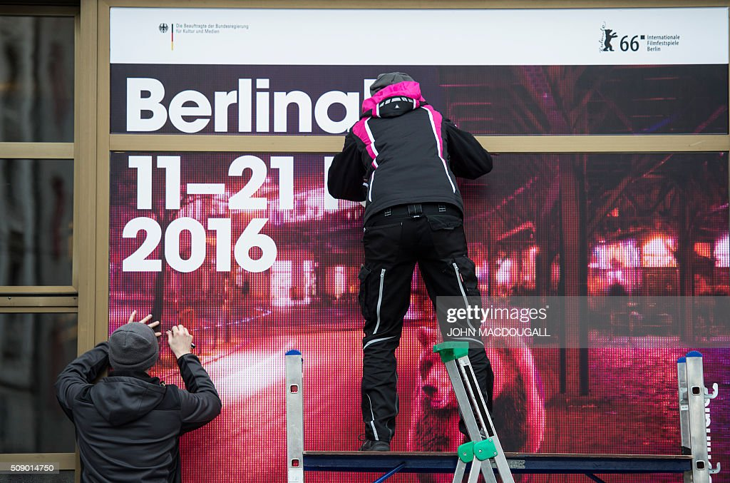 Workers puts up a poster advertising the Berlinale Film Festival at the Friedrichstadt Palast theatre in Berlin on February 8, 2016. Movies starring Colin Firth, Kirsten Dunst and Emma Thompson will vie for gold at the 66th Berlin film festival starting February 11, with Meryl Streep as jury president and a spotlight on Europe's refugee crisis. / AFP / John MACDOUGALL