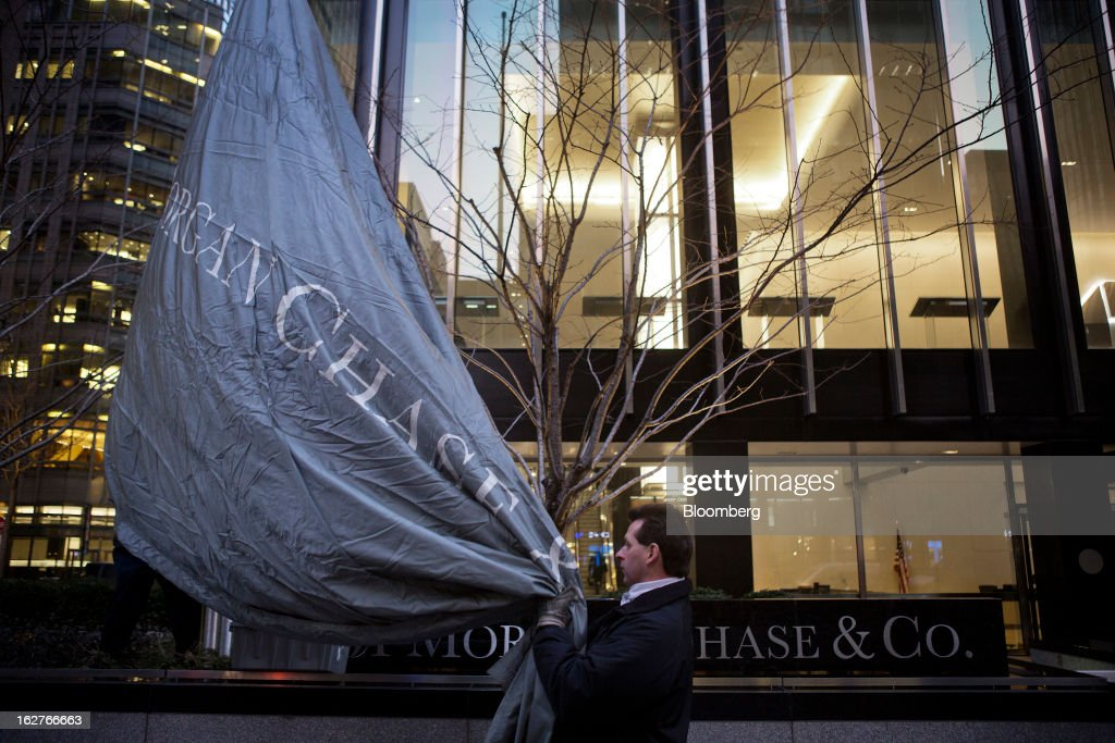 Workers raise a JPMorgan Chase & Co. flag at company headquarters before an annual Investors Day conference in New York, U.S., on Tuesday, Feb. 26, 2013. JPMorgan Chase & Co., the biggest U.S. bank, expects headcount to decline by about 4,000 in 2013 as Chief Executive officer Jamie Dimon targets mortgage operations for cuts. Photographer: Victor J. Blue/Bloomberg via Getty Images