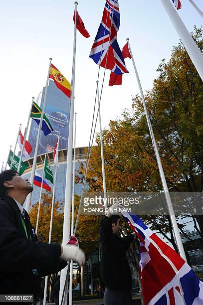 Workers raise a new Union Jack flag for Britain alongside other flags of the participating G20 countries outside the venue of the G20 Summit in Seoul...