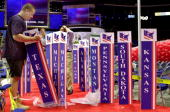 Workers raise delegate signs for the state delegations to the Republican National Convention in the First Union Center in Philadelphia Pennsylvania...