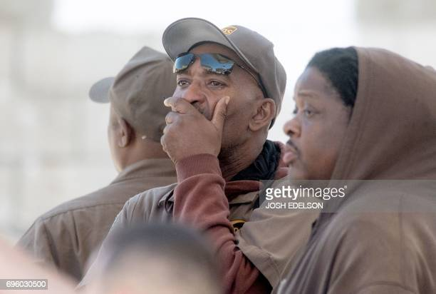 UPS workers react at the scene where a gunman shot and killed multiple people including himself at a UPS facility in San Francisco California on June...