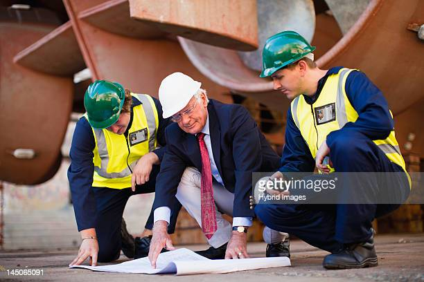 Workers reading blueprints on dry dock