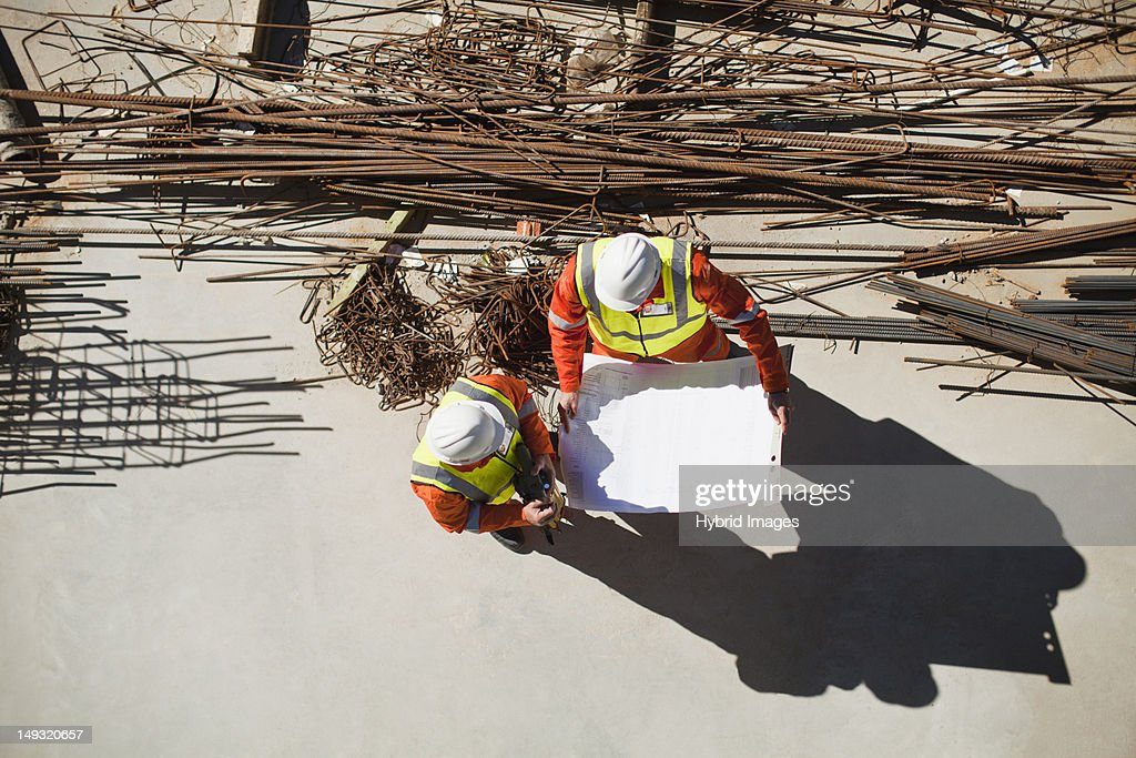 Workers reading blueprints on site : Stock Photo