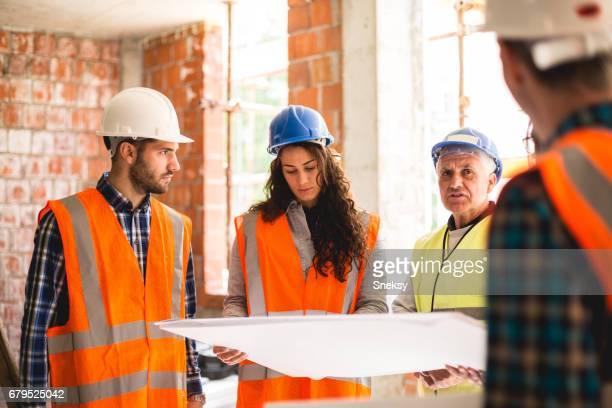 Travailleurs lecture de plan sur place