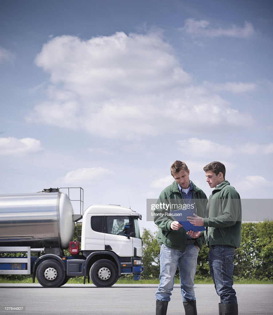 Workers reading clipboard by tanker