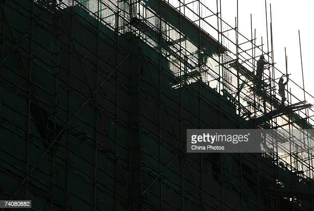 Workers reinforce scaffoldings around a building under construction on May 5 2007 in Nanjing of Jiangsu Province China Housing prices will continue...