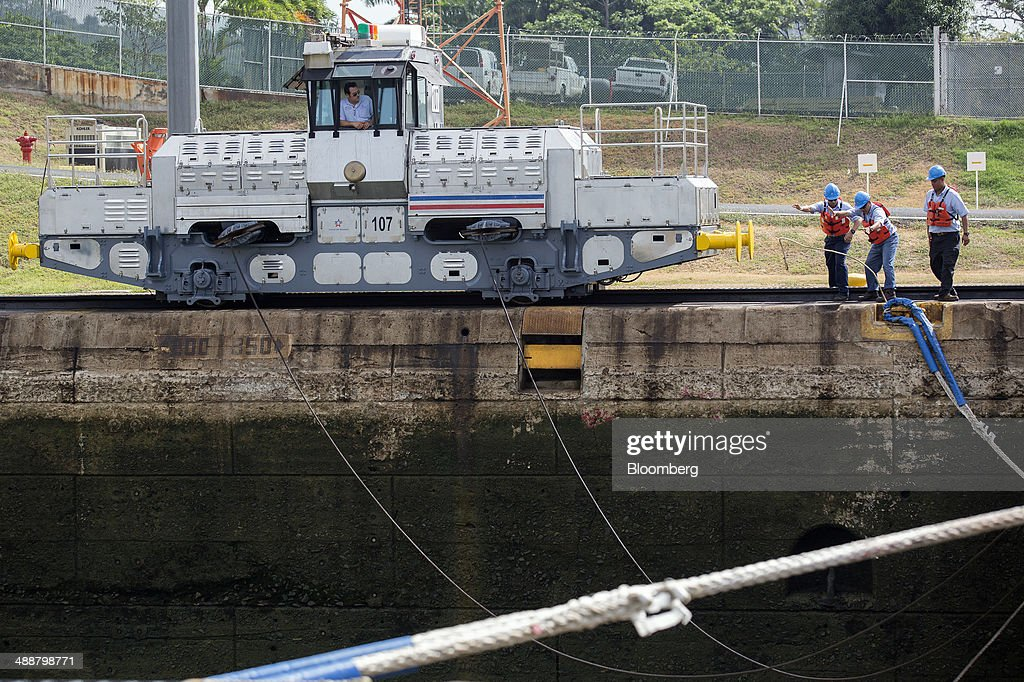 Workers release the ropes from a vessel as it passes through the Miraflores Locks at the Panama Canal near Panama City, Panama, on Wednesday, April, 23, 2014. Construction projects throughout Panama have remained idle since April 23, when workers walked off the job in an effort to win a 35 percent salary increase. The strike threatens to further delay the canals expansion, designed to accommodate larger ships and help reduce transport costs for commodities such as liquefied natural gas. Photographer: Susana Gonzalez/Bloomberg via Getty Images